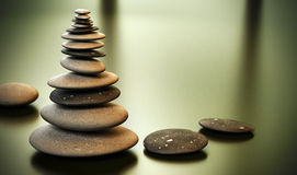 Pebble tower - Pebbles stack. Tall pebble stack over a yellow green background with room for text on the right side Royalty Free Stock Photography