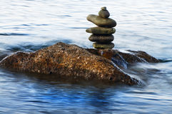 Pebble tower on rock in water. Pebble tower on rock in water with wave Stock Photography