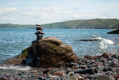 Pebble Tower with Sea in Background. Seascape image of pebbles stacked on a rock on the seashore with the coastline in the background Stock Images