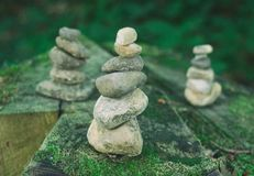 Pebble towers in a forest. Balanced stones in a pile on the wooden background covered with moss royalty free stock photography