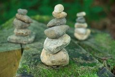Pebble towers in a forest. Balanced stones in a pile on the wooden background covered with moss stock photos
