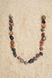 Pebble u letter  on sand Royalty Free Stock Photo