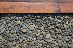 Pebble and wood plank. As background Royalty Free Stock Image