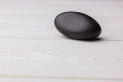 Pebble on a wooden table Royalty Free Stock Photos