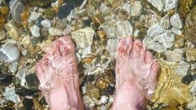 Босоногий человек стоит на pebbled seashore в воде Прибой ударяет ноги человека Воссоздание и туризм видеоматериал