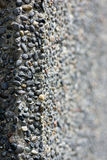 Pebbled texture. A pebbled concrete textured wall, selectively focused on the left side, blurring to the right side, ideal for copy Royalty Free Stock Photography