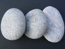 Pebbles. Three gray pebbles on a black background Royalty Free Stock Photos