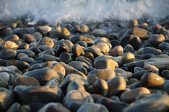 Pebbles. On the beach lit by the sun and a wave on the background Stock Photo