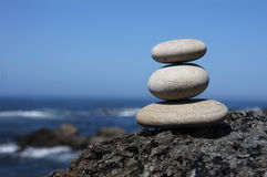 Pebbles. Stack on a volcanic rock near the sea Stock Images
