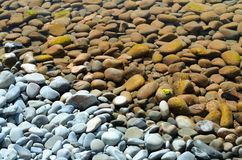 Pebbles above and under water. Smooth pebbles above and under water. Sea background Royalty Free Stock Images