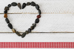Pebbles arranged as a heart on white wooden background with red. Heart shaped dark shades of stone, small pebbles arranged as a heart on white wooden background Stock Photography
