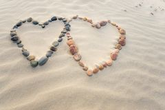 Free Pebbles Arranged In Shape Of Two Hearts On Sand Beach Ripples Stock Photos - 102850743