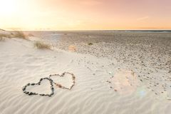 Pebbles arranged in shape of two hearts on sand beach ripples with beautiful sunset. Stones arranged in shape of two hearts on sand beach ripples with beautiful Royalty Free Stock Photos