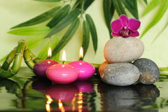Pebbles arranged in Zen lifestyle on the right with an orchid at the top and pink candles lit Stock Photos
