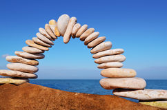 Pebbles in the balance. Arch of white pebbles in the balance on the seacoast Stock Photos