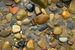 Pebbles on the Beach. Pebbles pattern in a pool of sea water on the beach Stock Photo