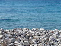 Pebbles on beach. With sea in background Royalty Free Stock Photo