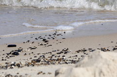 Pebbles on the beach. In the background approaching wave foam, pebbles lying on the wet sand Royalty Free Stock Photos