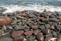 Pebbles on the Beach Being Washed by Wave Royalty Free Stock Photography