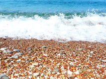 Pebbles on the beach and big wave Stock Images