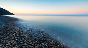 Pebbles on beach causing the sea to flow around them making patterns Royalty Free Stock Photography