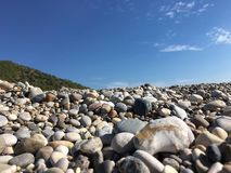 Pebbles on the beach. Different pebbles near the sea against the sky and mountains Stock Photography
