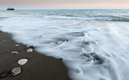 Pebbles in the beach and flowing sea water Stock Photography