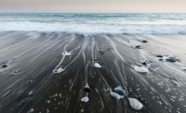 Pebbles in the beach and flowing sea water Royalty Free Stock Image