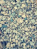 Pebbles at the beach. Photography of pebbles on the beach, is not the true color has been used a filter to modify the contrast and light saturation Royalty Free Stock Images