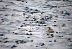 Pebbles on the beach randomly on the sand. Small, smooth pebbles settle in the sand on the beach Stock Photo