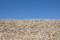 Pebbles on beach 1. Pebbles on the beach on a sunny day with a blue sky in the background. Space for text Stock Image
