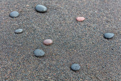 Pebbles on black sand beach in Padangbai, Bali Island, Indonesia Stock Photos