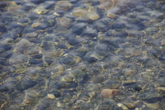 Pebbles brown and black color under the water. Pebbles brown and black color under the sea water, the incoming wave from above Stock Photos