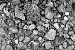 Texture of stones on the beach. Pebbles chaotically scattered on the beach in monochrome in winter Stock Photos