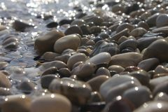 Pebbles close up shimmering in the sun with a blurry background.  stock image