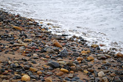 Pebbles at the coast. And the ocean Royalty Free Stock Photos