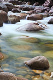 Pebbles in creek flowing water Stock Images