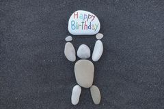 Pebbles design man holding a stone with the carved and colored message for a Happy Birthday Royalty Free Stock Image
