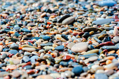 Pebbles of different colors on the beach closeup stock photo