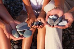 Pebbles in family with girl hands Royalty Free Stock Images