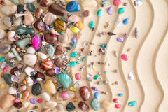 Pebbles, gemstones and shells on beach sand. Pebbles, gemstones and shells scattered in a decorative arrangement on tropical golden beach sand with a ridged Royalty Free Stock Photo