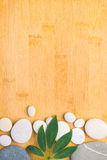 Pebbles and green leaf on the bamboo Royalty Free Stock Images