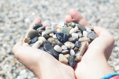 Pebbles in hands, heart pebble shape Stock Photos