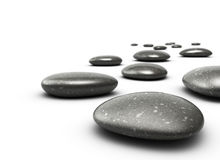 Pebbles, harmony and meditation. Many pebbles on a white floor, stones are black with grey dots, there is a blur effecton the background, the front stone is Stock Photography