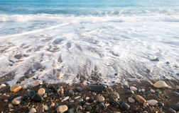 Free Pebbles In The Beach With Soft Milky Sea Water Royalty Free Stock Images - 74638219