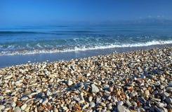 Pebbles på en sandig strand Royaltyfri Fotografi