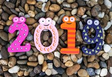 Pebbles pattern or small stones background in garden with colorful Arabic wooden numbers; 2019. Concept of new year and textured. Pebbles pattern or small stones stock photos