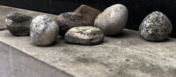 Pebbles resting on a plane surface. Random sized pebbles royalty free stock photos