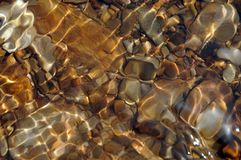 Riverbed Pebbles Wave. Pebbles on a river bed. Reflections and ripples on the surface. riverbed pebbles wave water wet river nature stock image