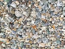 Pebbles rocks stones wet beach textured background stock photo